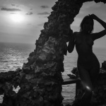 Naked young model on the rocks. Sunset and ocean
